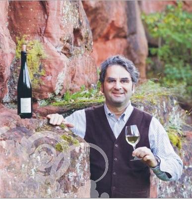 グラスに注がれた葡萄ジュースを片手に持つ生産者の写真