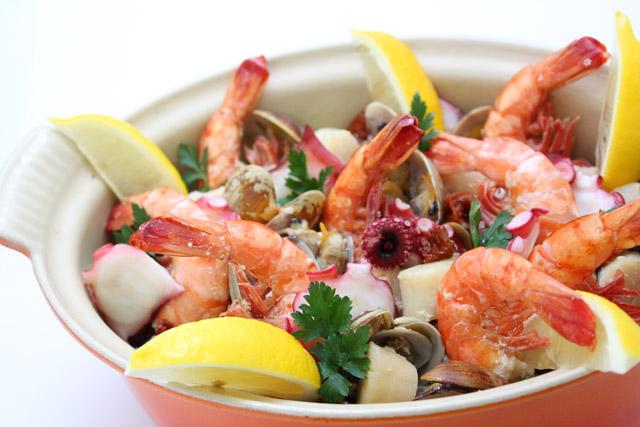 オレンジ色のルクルーゼに盛りつけられた海老やタコ、貝類やレモンの炊き込みご飯の写真