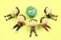 地球儀を囲む5人の人の写真