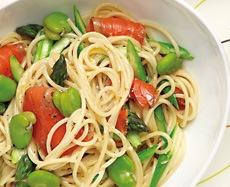 白い器に盛られた空豆、サーモン、アスパラガスのスパゲッティーの写真