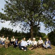 自然の中で9人の生産者が葡萄ジュースを片手に持っている写真