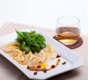白角皿に盛り付けられたカルパッチョとグラスに入ったドリンクの写真