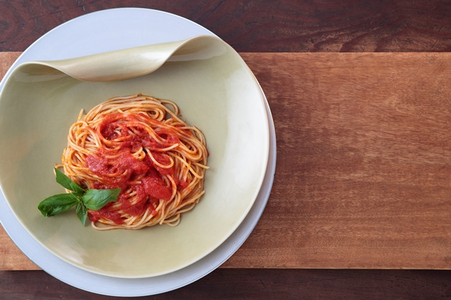 丸皿に盛りつけられたチェリートマトのソースを使ったトマトパスタの写真