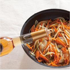 炒めた野菜にホワイトバルサミコ酢をかけている調理写真