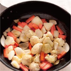 オリーブオイルで揚げた野菜にホワイトバルサミコ酢をかけている調理写真