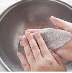 旬の魚に小麦粉を薄くまぶしている調理写真