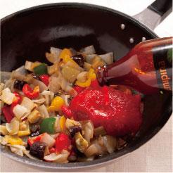 炒めた野菜にチェリートマトのソースを加えている調理写真