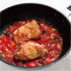 チェリートマトのソースで鶏肉を煮込んでいる調理写真