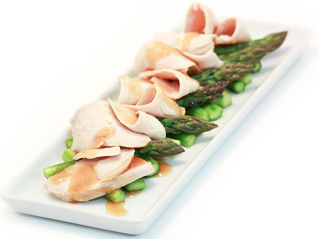 白い長方形皿にアスパラガスと枝豆を敷き塩鶏肉を乗せた写真