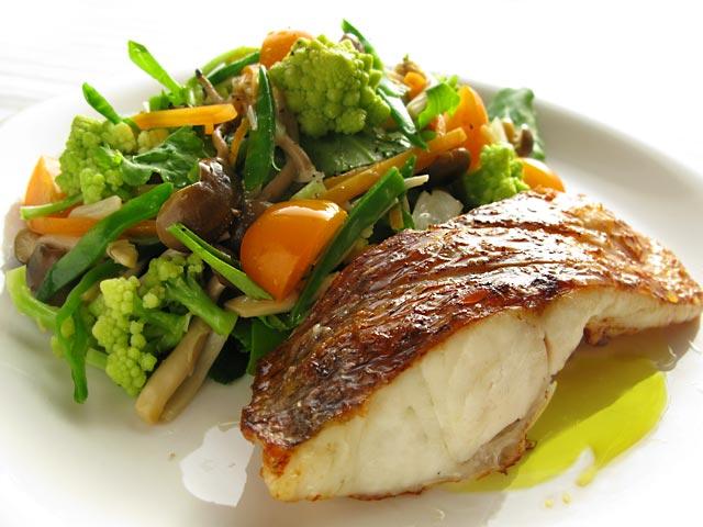 丸皿に盛りつけられた白身魚のグリルと野菜の料理写真