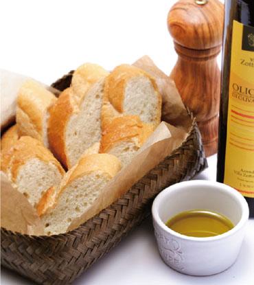 カゴに入った薄切りのフランスパンのとなりにオリーブオイルの瓶、ソルトミル、小皿に注がれたオリーブオイルが並んでいる写真